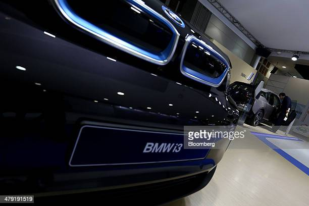 A visitor looks inside a Bayerische Motoren Werke AG i3 electric vehicle on display at the first International Electric Vehicle Expo in Seogwipo Jeju...