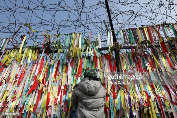 A visitor looks over a ribbon wishing for reunification of the two Koreas on the wire fence at the Imjingak Pavilion near the demilitarized zone...
