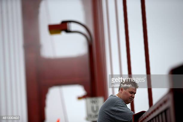 A visitor looks over the railing on the Golden Gate Bridge on June 27 2014 in San Francisco California The Golden Gate Bridge district's board of...