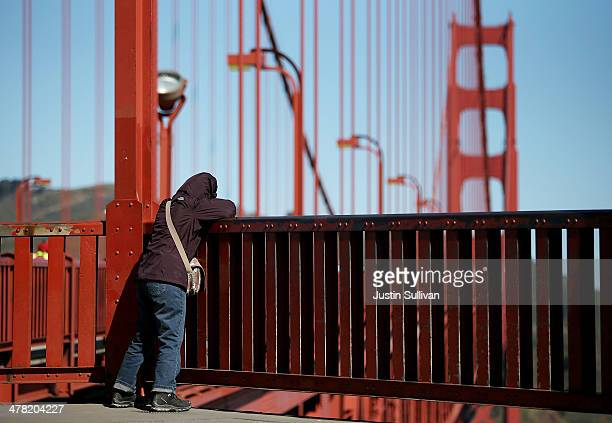 A visitor looks over the railing on the Golden Gate Bridge on March 12 2014 in San Francisco California A long debated suicide barrier on the Golden...