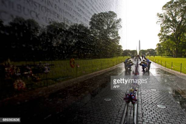 TOPSHOT Visitor looks the names on the wall of the Vietnam Veterans Memorial in Washington DC May 28 2017 Motorcyclists are in Washington for the...