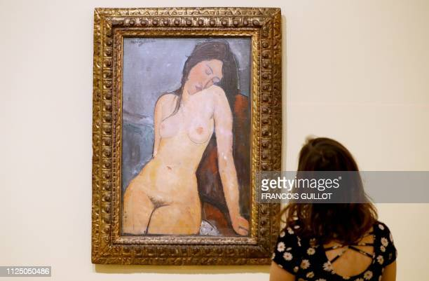 A visitor looks the painting 'Seated Nude ' by Italian artist Amedo Modigliani during the press visit of the exhibition 'The Courtauld Collection A...