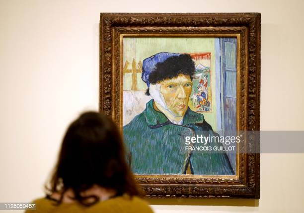 A visitor looks the painting Self Portrait with Bandaged Ear by Dutch painter Vincent Van Gogh during the press visit of the exhibition The Courtauld...