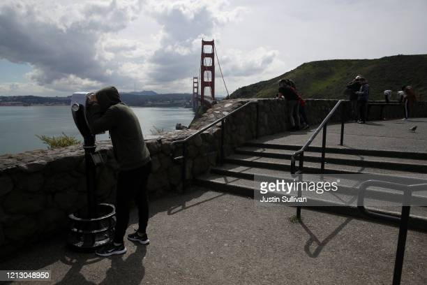 Visitor looks through binoculars near the Golden Gate Bridge on March 17, 2020 in Sausalito, California. Seven San Francisco Bay Area counties have...