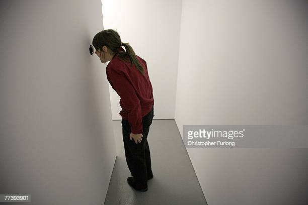 A visitor looks through the peep hole of Turner Prize nominated work Amnesiac Shrine or 'The Misplacement mirrored cubes inverted with the reflection...
