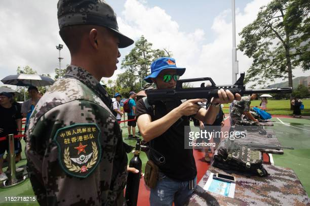 A visitor looks through the scope of a weapon during an open day at the People's Liberation Army Shek Kong Barracks in Hong Kong China on Saturday...