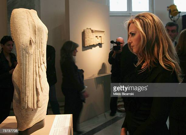 A visitor looks to a marble Parian woman's torso from the 6th century BC as it is displayed during its official presentation along with other...
