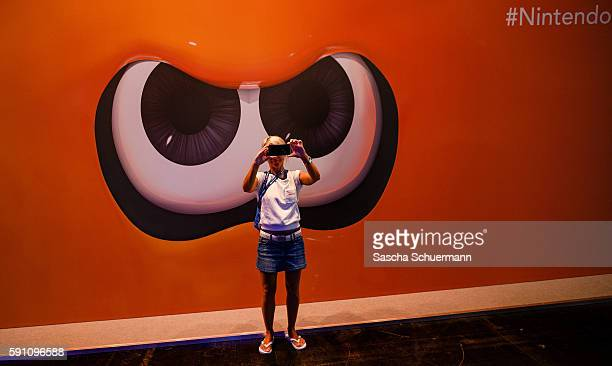 A visitor makes a selfie in front of the Nintendo stand at the Gamescom 2016 gaming trade fair during the media day on August 17 2016 in Cologne...