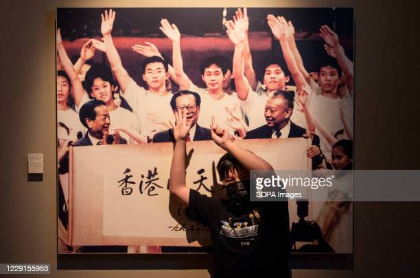 """Visitor makes pro-democracy gestures in front of a portrait of former Chinese leader Jiang Zemin at the exhibition """"The Hong Kong Story"""" at the Hong..."""