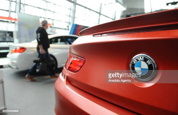 A visitor of BMW World walks past a BMW car during the annual accounts press conference of German car manufacturer BMW at the BWM World in Munich...