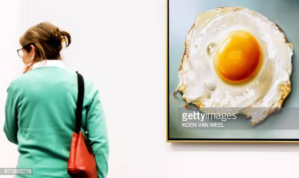 A visitor of the exhibition Hyperrealism 50 years stands next to the work 'Fried Eggs' of Dutch artist Tjalf Sparnaay in the Kunsthal museum in...