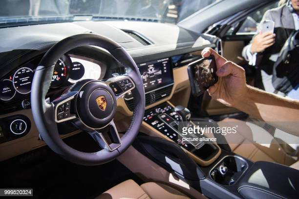 A visitor of the premiere photographs the interior of the car model during the introduction of the new Cayenne Generation at the Porsche Museum in...
