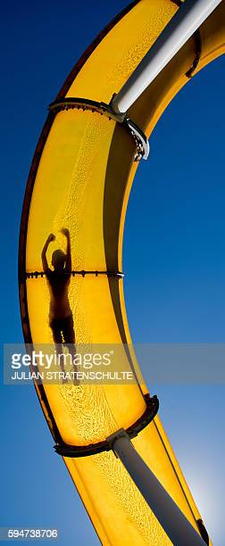 A visitor of the 'Suedbad' public open air swimming pool slides down into the refreshing water on August 24 2016 in Hameln northern Germany / AFP /...