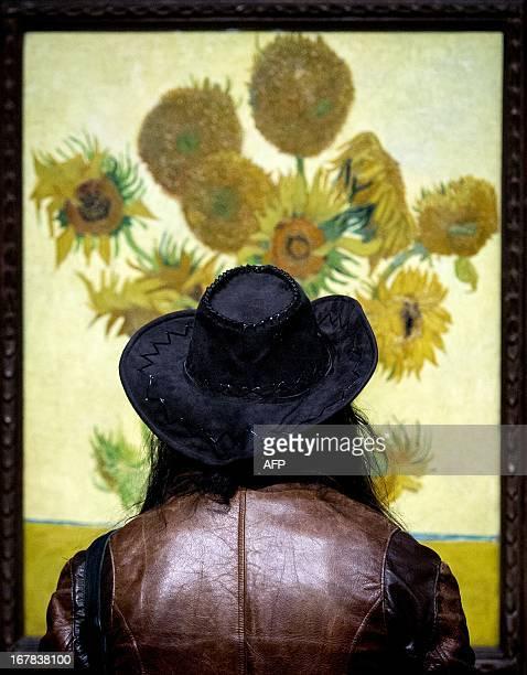 A visitor of the Van Gogh Museum Amsterdam looks at The Sunflowers painting by the Dutch artist during the reopening of the museum in Amsterdam on...