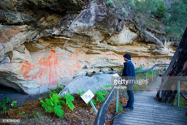 Visitor on boardwalk looking at Aboriginal rock paintings in the Tombs a sacred area used as a burial site by the Aboriginal inhabitants of the...