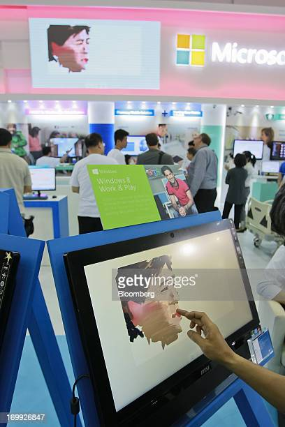 A visitor paints on a MicroStar International Co AllinOne PC at the Microsoft Corp booth at Computex Taipei 2013 in Taipei Taiwan on Tuesday June 4...