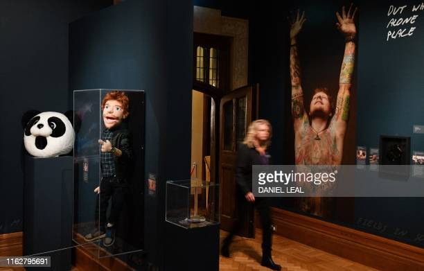 A visitor pases photos items relating to British musician Ed Sheeran during a press preview of the exhibition 'Ed Sheeran Made in Suffolk' in Ipswich...