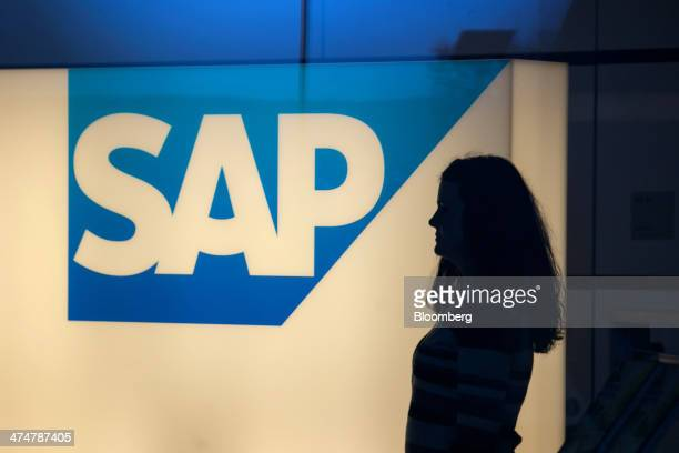A visitor passes an illuminated SAP AG logo inside the businesssoftware maker's headquarters in Walldorf Germany on Monday Feb 24 2014 SAP AG coChief...