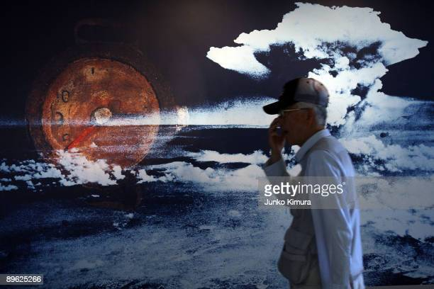Visitor passes by a wall displaying a picture of the mushroom cloud when the atomic bomb was dropped over Hiroshima in 1945, at the Peace Memorial...