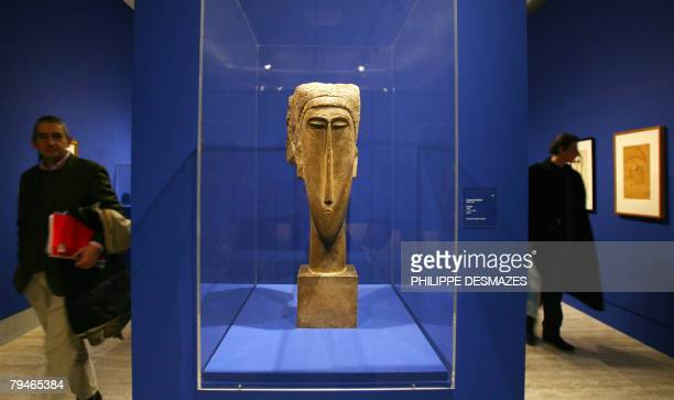 "Visitor passes by 'Head', a sculpture by Italian painter Amedeo Modigliani at the opening of an exhibition ""Modigliani and his times"" at the..."