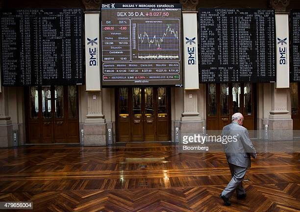 A visitor passes Ibex 35 stock price information as sits displayed on electronic screens inside the Madrid Stock Exchange also known as Bolsa y...