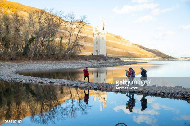 Visitor passes the Rhine River on a path as a result on low water next to the Mouse Tower on November 13 2018 in Bingen Germany Summer heat wave in...