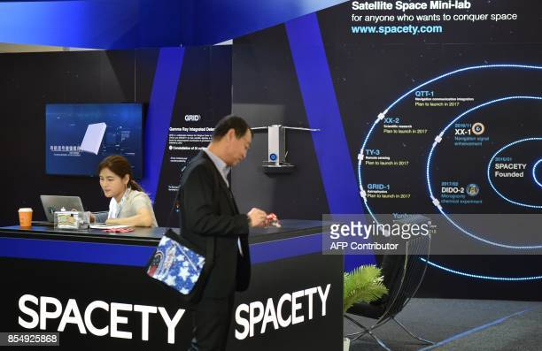 A visitor passes the stand of an exhibitor at the 68th International Astronautical Congress 2017 in Adelaide on September 28 2017 The 68th...