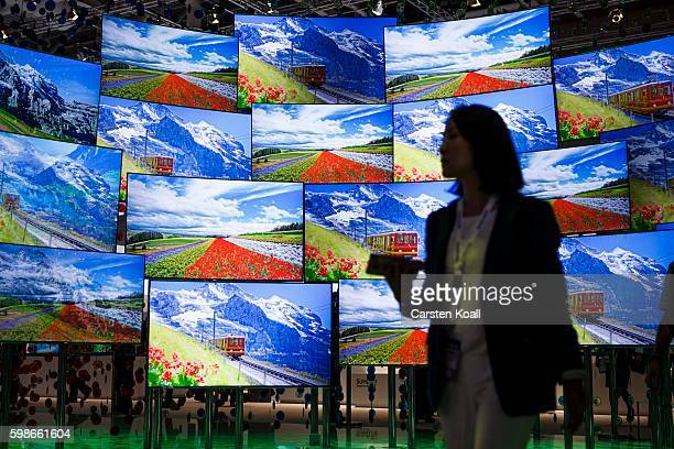 A visitor passing the display wall from Samsung at the 2016 IFA consumer electronics trade fair on September 2 2016 in Berlin Germany IFA is among...