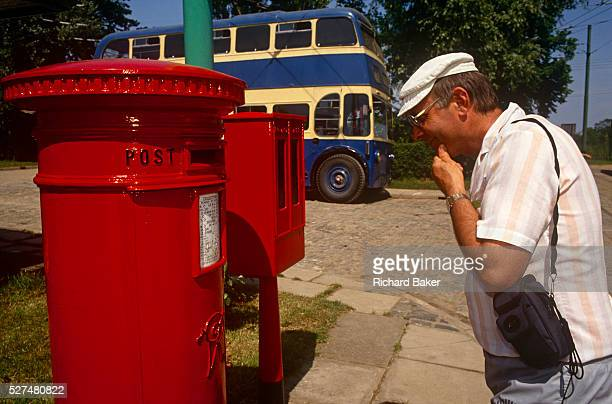 A visitor pauses to read the writing on a Royal Mail postal box while walking round the East Anglia Transport Museum Lowestoft Suffolk England A...