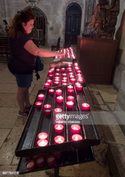 A visitor pays for candles at the Se de Lisboa the city's cathedral on June 18 2017 in Lisbon Portugal Although active all year round Portuguese...