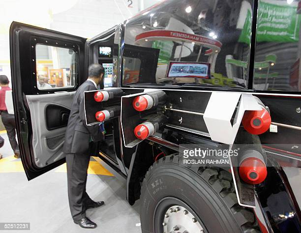 A visitor peek inside an armoured car Smartruck III which equipped with missiles on display at the Global Security Asia 2005 conference and...