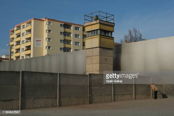 A visitor peeks from the inner wall into the death zone under an original East German guard tower at a preserved portion of the Berlin Wall at...