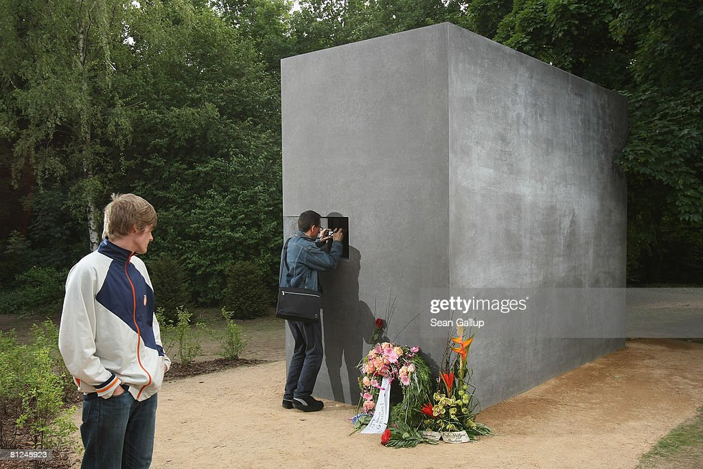 A visitor peeks into the window of the newly-inaugurated memorial to homosexual victims of the Nazis on May 27, 2008 in Berlin, Germany. The memorial, a large stone with a window that looks onto an image of two men kissing, commemorates the tens of thousands of gays imprisoned by the Nazis, including the estimated 15,000 sent to concentration camps. The memorial stands in the Tiergarten park close the to Holocaust Memorial.