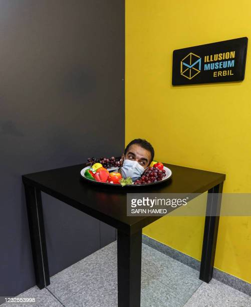 Visitor peeks out of a bowl of fruit, part of an optical illusion installation, at the Illusion Museum in Arbil, the capital of Iraq's northern...