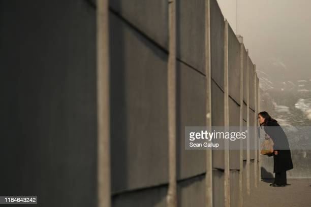 A visitor peeks through slats in the inner wall into the death zone at a preserved portion of the Berlin Wall at Bernauer Strasse on October 31 2019...