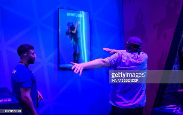 A visitor performs at the stand of facebook gaming in front of a videoscreen with the lettering infinite dab during the media day of the Gamescom...