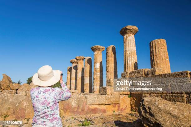 visitor photographing the temple of heracles (temple of hercules), unesco world heritage site, valley of the temples, agrigento, sicily, italy, mediterranean, europe - agrigento stock pictures, royalty-free photos & images