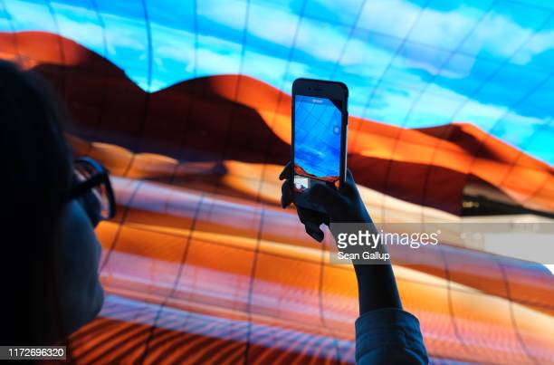 Visitor photographs a display of curved OLED televisions at the LG stand at the 2019 IFA home electronics and appliances trade fair on September 06,...
