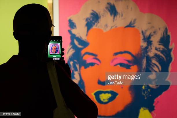A visitor photographs a screen print of Marilyn Monroe entitled 'Marilyn' by Andy Warhol at the 'Andy Warhol Pop Art' exhibition at the RCB Galleria...