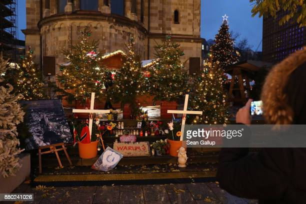 A visitor photographs a small memorial to terror victims at the annual Christmas market on its opening day at Breitscheidplatz where approximately a...