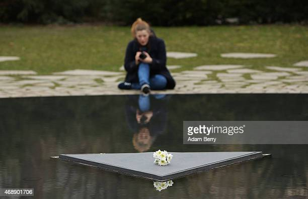 A visitor photographs flowers placed for Romani victims of the Nazis on a reflecting pool at the Memorial to the Sinti and Roma of Europe Murdered...