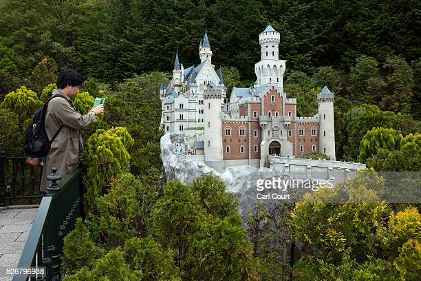 A visitor photographs Neuschwanstein Castle at Tobu World Square theme park on May 01 2016 in Nikko Japan Tobu World Square contains over a hundred...