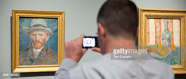 Visitor photographs on smartphone self portrait by Vincent Van Gogh at Rijksmuseum Amsterdam Holland