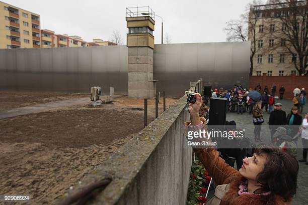 A visitor photographs over the edge of a stillexisting section of the Berlin Wall into the socalled 'death strip' where East German border guards had...