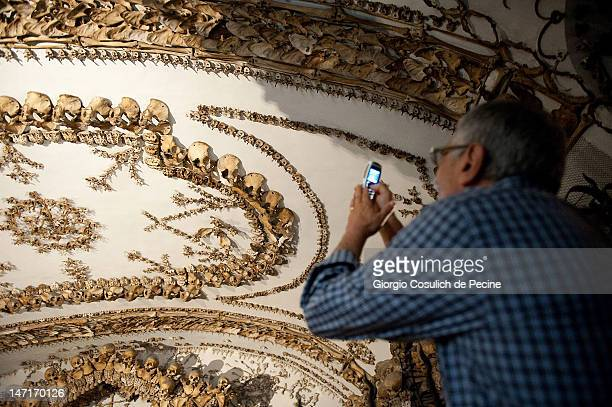A visitor photographs the ceiling decorations of the crypt made with the bones of Capuchin monks during the opening of the museum in the Capuchin...