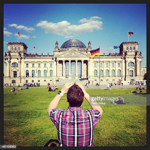 A visitor photographs the Reichstag on April 28 2014 in Berlin Germany The Reichstag home of the Bundestag the German parliament is among the city's...