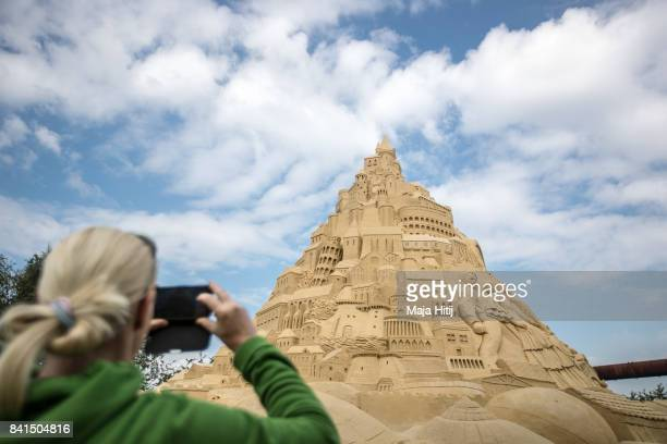 Visitor photographs the Sandburg sandcastle on September 1 2017 in Duisburg Germany A local travel agency commissioned the building of the sandcastle...