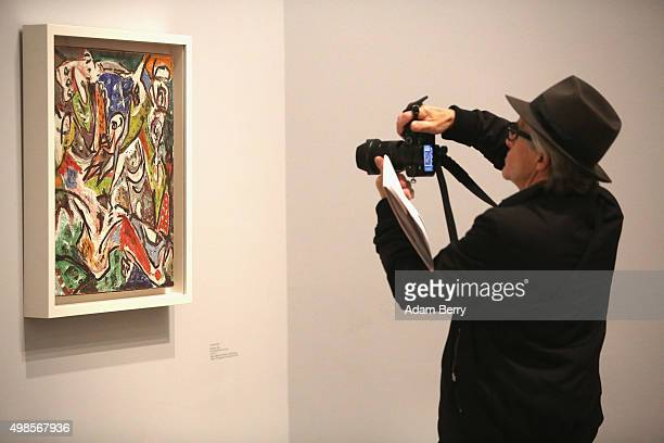 A visitor photographs the work 'Bird Effort' 1946 by Jackson Pollock during a press preview of the 'Jackson Pollock's Mural Energy Made Visible'...