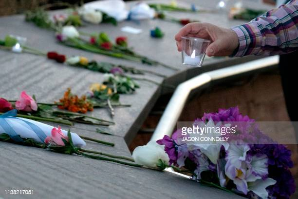 TOPSHOT A visitor places a candle among flowers at the Columbine Memorial at Clement Park in Littleton Colorado during a community vigil for the 20th...