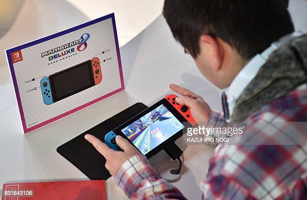 A visitor plays a Nintendo's new Switch game console during its game experience session in Tokyo on January 14 2017 Nintendo on January 13 unveiled...